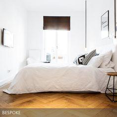 Das Weiß des Betts und der Wände harmonieren zum alten Fischgrätboden aus Eiche. Eingerichtet von BESPOKE Stefan Neubrand Innenarchitekten aus München. #Schlafzimmer #weiß
