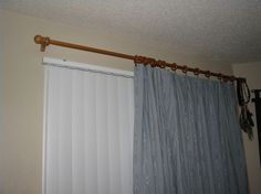 Curtains over vertical blinds- Place the center support for the curtain rod in the center of the window, also about 4 inches above the vertical blind.