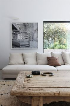 rug, low natural wood coffee table, picture adjacent to window