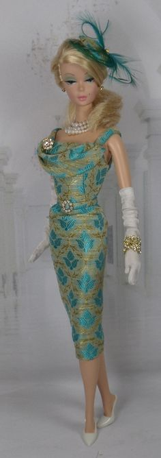 A vintage style cocktail sheath cut from pure silk brocade, fully lined in china silk, with draping front adorned with a rhinestone brooch.