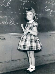 Writing on the chalkboard, 1950's. This actually looks like me in the First Grade ... same hairdo, same outfit (ltm)