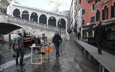 A man sells Wellington boots in flood waters near Rialto Bridge during a period of seasonal high water in Venice Wooden Walkways, Rialto Bridge, Wellington Boot, High Tide, Places To Travel, Venice, Street View, Explore, City