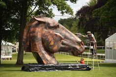 Nic Fiddian-Green Photos - Artist Nic Fiddian-Green puts the finishing touches to his sculpture 'Copper Horse' as it is installed in the Royal Enclosure at Ascot Racecourse on June 14, 2013 in Ascot, England. The 'Royal Ascot' race meeting will take place at the racecourse from 18 - 22 June, 2013. - Sculptures Arrive at the Ascot Racecourse