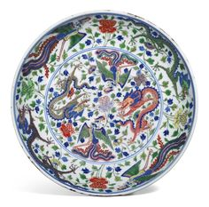 WUCAI 'DRAGON AND PHOENIX' DISH KANGXI MARK AND PERIOD, the rounded sides rising to a slightly everted rim, the interior painted with a pair of five-clawed dragons and a pair of phoenix amidst scrolling, leafy stems of peony 31.7cm