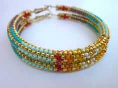"""""""L.E.S. Artistes"""" 2.75-in. peyote stitched beaded hoops. Size 15 beads with 14k gold Charlotte cut beads. Artist:  Andrea Preston (Navajo)"""