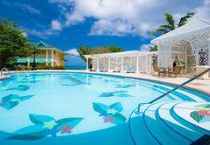 Romantic trellis-style cabanas line the main pool. | Sandals Resorts | Jamaica