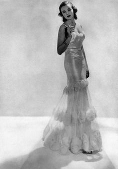 December 1936, smoking in an evening dress with white silk net and mousseline roses designed by Sally Milgrim.