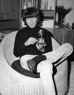 George Harrison playing with one of the many awards he has received for his music making