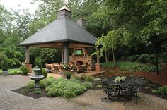 Gazebo with outdoor fireplace and TV by Neal's Design Remodel.
