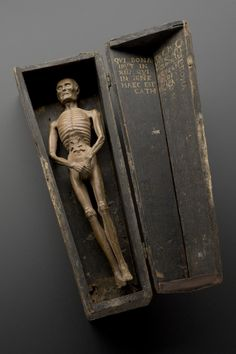 Figure of a man in a coffin, Italy, 1501-1600    Carved from wood, this figure shows a male corpse inside a coffin. The body is in advanced decay and worms are spilling from the stomach. The coffin is a memento mori. This is an object that reminds the viewer of the shortness of human life and the inevitability of death.
