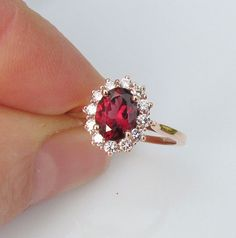 Appraisal for the following ring for Chris: Main Stone: 7x5mm oval (diamond carat equivalent 0.75 to 1ct), genuine red spinel. For those of you not familiar with the beautiful spinel, please read this blog: http://pristinegemstonejewelryintro.blogspot.ca/2012/11/spinels-take-closer-look.html Mount #71606, 14k rose gold, set with 12, 1.90mm round GH SI1 quality diamonds. Ring size: ring is made to order so it will be custom made to fit. Please allow 3 weeks for completion. Welcome to…