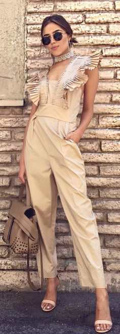 Olivia Culpo's tan pleated jumpsuit, lace jewelry, tan handbag, and nude sandals