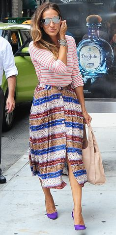 Sarah Jessica Parker proved she was a street style star when she was snapped out and about in NYC in a red-and-white striped top that she expertly paired with a full buttoned chunky striped midi-length skirt, complete with aviators, her usual stack of bracelets, a neutral handbag and violet purple pumps.