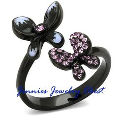 Adorable Flutterby Butterfly Ion Black Plated Stainless Steel Ring – Jennies Jewelry Chest  This is simple yet stunning ring. It features two delicate butterflies, set on an ion black plated stainless steel band. One butterfly features the sparkle of light purple czs, while the second just has a cz in the center.