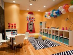HOME DECOR: A giant painted gumball machine pops against the vibrant orange walls of this lively playroom. Along with the wall color, the artistic paper lantern fixture, chevron rug, and art table are enough to inspire hours of creative play. Creative Kids Rooms, Creative Play, Colorful Playroom, Chevron Rugs, Cool Kids Bedrooms, Toy Rooms, Kid Spaces, My New Room, Kids Rugs