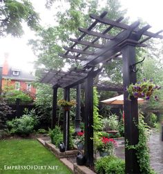 Tall columns support narrow arbors to define this patio from the garden.