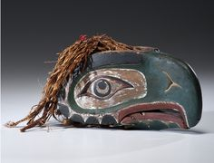 Kwakwaka'wakw Vintage Hand Puppet - sold for $14,687.50; carved cedar eagle head w articulated lower bill controlled by wooden apparatus inside head; sculpture secured with rusty nails & painted w red, dark green, white, black pigments; shredded cedar bark that has been tied together with faded red fabric is positioned on top of head,12 in. x 6.25 in.  late 19th century      Puppet exhibited as cover lot in René Rasmussen's auction, Paris: March 19, 1980