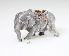 Lot# 1157 A Russian silver, diamond and ruby elephant-form match holder. 1908 - 1917, St. Petersburg, 88 standard silver, with spurious maker's marks, realistically modeled with bow-tied laurel swags to sides, 2'' H x 3'' W x 1.5'' D, 5 oz, est: $500/700 *Price Realized: $1,347.50