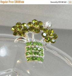 This #vintage green rhinestone flower brooch is just  gorgeous!  It features a silver tone flower basket filled with   olivine green rhinestone flowers in a peridot green rh... #ecochic #etsy #jewelry #jewellery