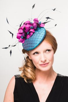 Janie A vibrant teal silk button with navy veiling overlay, decorated with a spray of bright magenta hand sewn flowers with navy chopped scattered veiling, finished with delicate clusters of navy coq feathers. A fabulously colourful, feminine and ornate design.