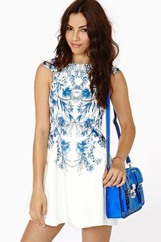 Blue and white graphic dress with a blue shoulder bag.