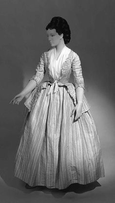 This is an example of one form of dress which became acceptable in the later part of the 18th century. The bodice is more like a jacket, known as a caraco. The informal sensibility about it is relative to the open robes and exposed petticoats of the period. The sleeves are known as sabot sleeves because they fit over the elbow like a sabot shoe, also known as a clog