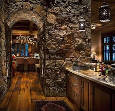 The stone arch gives this rustic bar nook an underground grotto feel.