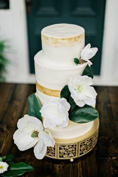 gold brushed wedding cake with magnolia flowers