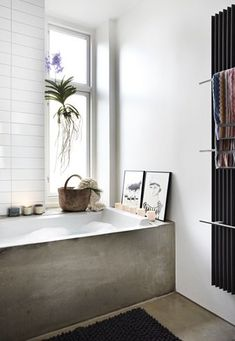 cement-sided tub. white tiles. tall, narrow window. greens. picture frames.