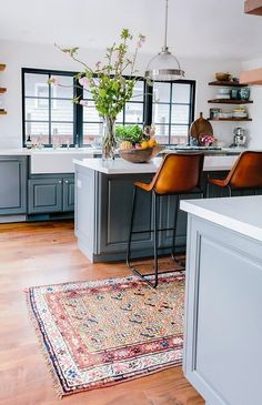 Modern kitchen with light gray cabinents, camel leather bar chairs, and a large aztec rug