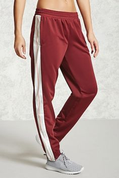 """An athletic pair of woven pants featuring a """"Realest"""" graphic down the sides, contrast side stripes, an elasticized waistband with a concealed drawstring, zippered on-seam pockets, and zippered trim at the cuffs."""