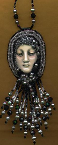 """Claire McGraw is a bead artist and sales representative for """"The Face"""". Shown here is a piece of wearable bead art created by Claire using the ceramic face. The faces are made by Diane Briegleb and come in a variety of color and glaze finishes."""