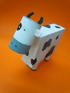 Una caja, rollo de cartón y pinturas para crear una vaca.