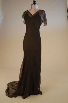 Black chiffon evening gown, circa 1930, with labelled black satin petticoat, the bias-cut gown with overall latticed bands and lace insert; together with a pair of black lace cami-nickers. Hartnell