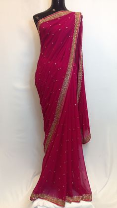 Stylish and gorgeous Georgette pink saree with beautiful golden blue contrast border along with hand designed embroidered beaded motifs makes this indian apparel to die for. High in demand due to its