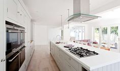 French windows and bi-fold doors fill the room with natural light  Hob and sink on the island to look out to the garden