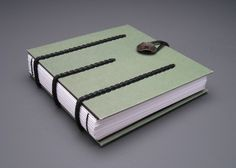 """Book on Leather Cords by Theresa Marr.   6.25"""" x 6.25"""" x 1.5"""" Binders Board, Leather Cording, Brass, Thread, Paper 2009"""