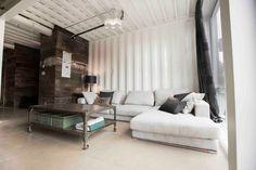 table basse style industriel en métal riveté avec boîtes de rangement vertes, dans le salon aménagé avec un canapé blanc et lambris mural bois