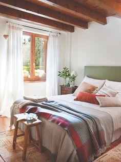 Dormitorio rústico con vigas de madera y paredes en blanco