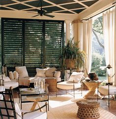 Sophisticated modern elegance. The use of shutters, columns and full length drapery feature the height and volume of this outdoor living room.