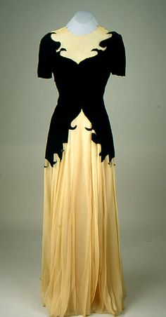 Dress 1940s; black velvet and beige net, for evening wear. Beige net fabric at neckline and skirt, with black velvet on sleeves, bodice and hips. Rounded neckline with center back closure, single self covered button and loop. Black velvet forms a sweetheart neckline over the netting. Short sleeves. Full skirt in net is lined with peach acetate. Proper left side zipper closure. Floor length.