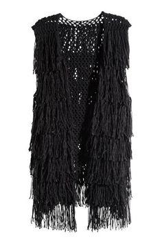 Chaleco con flecos: Chaleco en tejido calado y suave con lana en la trama. Flecos largos y sin cierre.