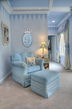 This regal, prince-themed nursery features baby blue, creamy white and silver to give it an ethereal appeal. A cozy velvet glider with a matching ottoman provides the perfect spot for mother and baby to bond.