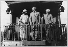 Warren G. Harding, full length portrait, standing on back of Northern Pacific train, facing left; with wife and Gardener, departing.