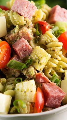 Easy Pesto Pasta Salad Recipe ~ tossed with creamy basil pesto dressing, grape tomatoes, chunks of salami, and cubed mozzarella cheese.