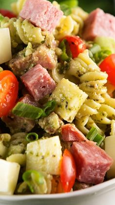 Easy Pesto Pasta Salad Recipe ~ tossed with creamy basil pesto dressing, grape tomatoes, chunks of salami, and cubed mozzarella cheese.