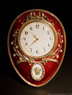 Clock by Fabergé. Here the lilies-of-the-valley motif appears incorporated into the design of the clock. The back of the frame is ivory with gold easel and clock-work casing.