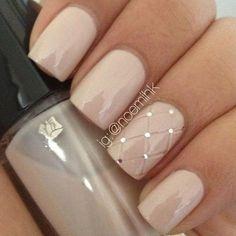 Elegantes uñas en beige, una de ellas decorada con diseños de rombos y brillos plateados