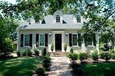 Beige brick, white columns, and black shutters.