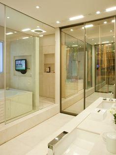 Esta sala de banho idealizada por Toninho Noronha tem 15 m² e une banheiro e closet no mesmo espaço. A área de banho é protegida por uma folha de vidro de correr, que isola o chuveiro (ao fundo) ou a banheira. Piso e paredes foram revestidos por mármore crema marfil jateado. A bancada, em forma de ilha, separa o quarto do banheiro. Com duas cubas, ela funciona como pia e cômoda e os espelhos fixos no forro completam a seção 'beauté'
